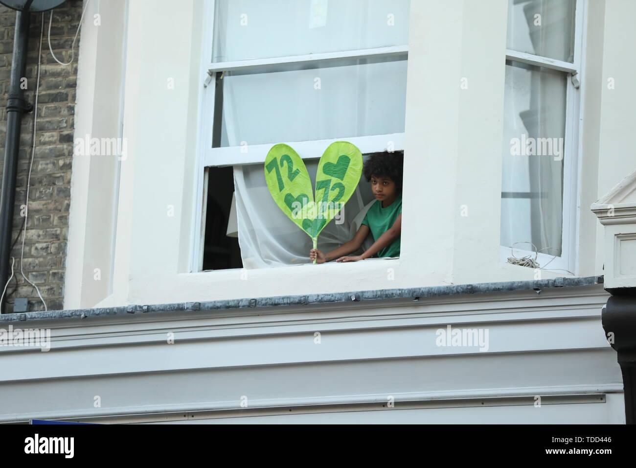 Ein Kind hält ein Plakat vor seinem Fenster, wie Familie und Freunde der 72 Menschen, die ihr Leben in der Grenfell Hochhaus Brand verloren nehmen Sie teil an einem ruhigen Spaziergang in London, anlässlich des 2-jährigen Jubiläum. Stockbild