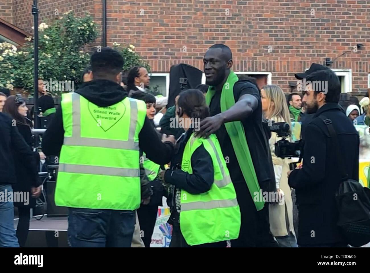 Rapper Stormzy Spaziergänge mit Familie und Freunden der 72 Menschen, die ihr Leben in der Grenfell Hochhaus Brand verloren, außerhalb Grenfell Tower, London, während ein stiller Spaziergang zum zweijährigen Jubiläum. Stockbild