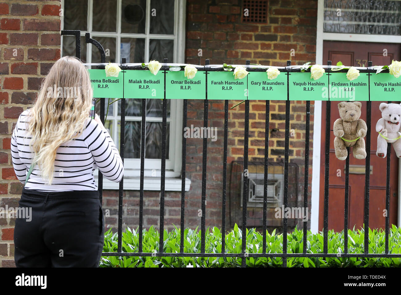 London, Großbritannien. 14 Juni, 2019. Eine Frau liest die Namen der Leute, die ihr Leben verloren, hing von einem Geländer auf einen Block von flachen während des Gedenkens. Die Grenfell Turm zweiten Jahrestag Gedenkfeier des Hochhauses Feuer. Am 14. Juni 2017, kurz vor 1:00 Uhr brach ein Feuer in der Küche des vierten Stock an der 24-stöckige Residential Tower Block in Kensington, West London, die das Leben von 72 Menschen. Mehr als 70 weitere wurden verletzt und 223 Menschen geflohen. Credit: SOPA Images Limited/Alamy leben Nachrichten Stockbild