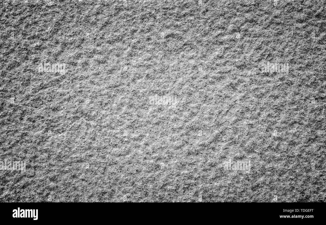 Nahaufnahme einer holprigen Granit stein Wand in Schwarz und Weiß mit Vignettierung. Hochauflösende full frame Hintergrund Textur. Stockfoto