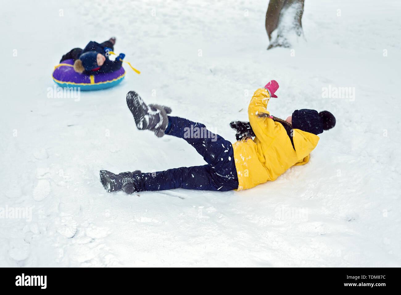 Glückliche Kinder fahren im Winter auf einem Schlitten schieben. Bruder und Schwester spielen zusammen. kids fiel und im Schnee gleiten Stockfoto