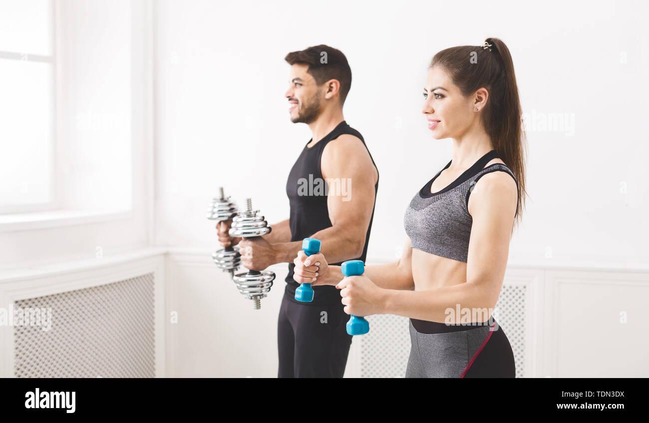 Dabei konzentriert Paar Übung mit Hanteln in Studio Stockfoto