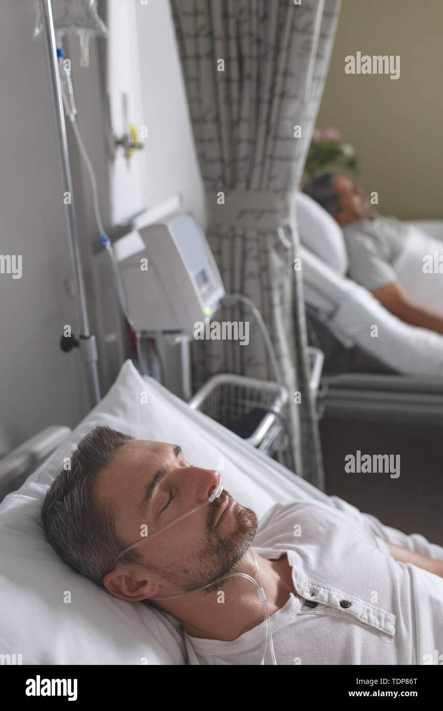 Männliche Patienten schlafen im Bett in der Station Stockfoto