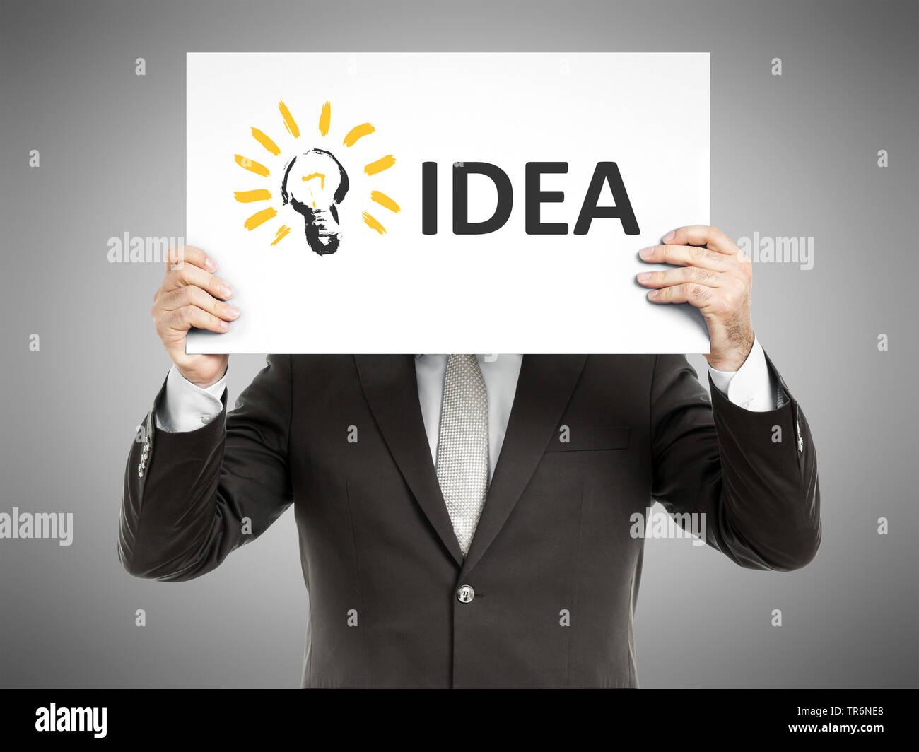 Geschaeftsmann haelt eine Schild vor sich mit der Aufschrift Idee, Idee, Deutschland | Geschäftsmann und hält ein Schild mit der Aufschrift Idee, Deutschland | Stockbild