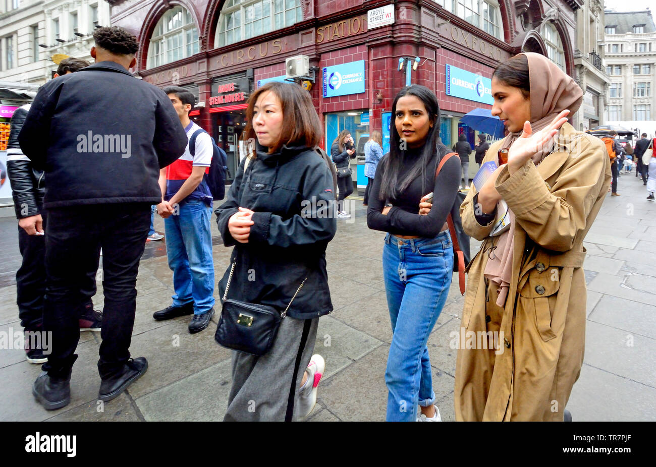 London, England, UK. Menschen verschiedener ethnischer Minderheiten Shopping in der Oxford Street an einem regnerischen Tag Stockbild