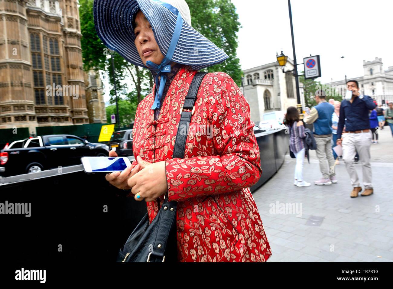 London, England, UK. Ältere asiatische Frau mit einem Mobiltelefon, Westminster Stockbild