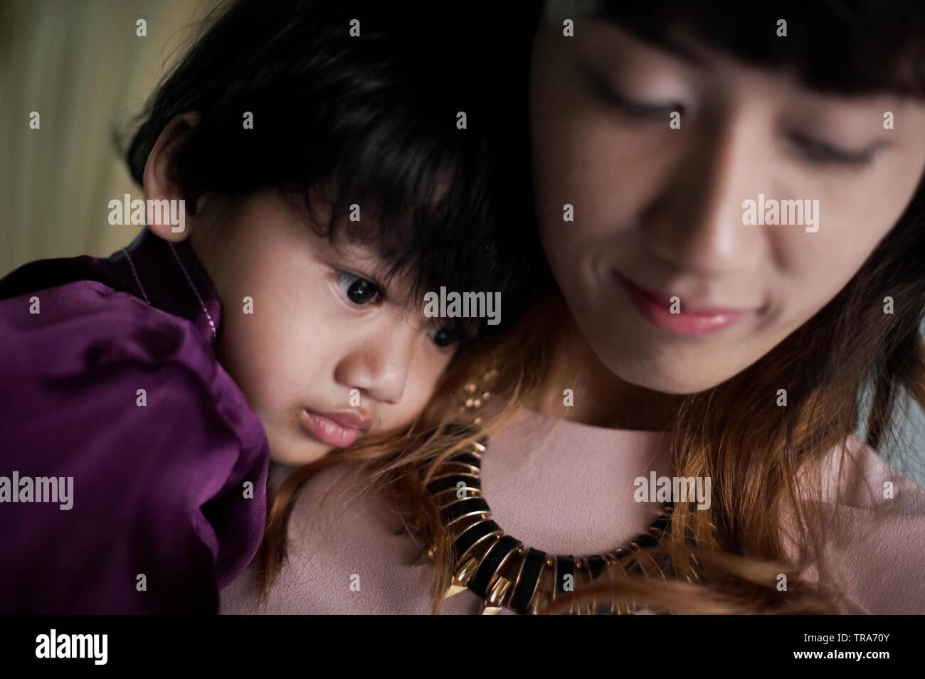Eine junge Malay Mutter liebevoll umarmt ihren kleinen Sohn auf dem Schoß sitzt. Stockfoto