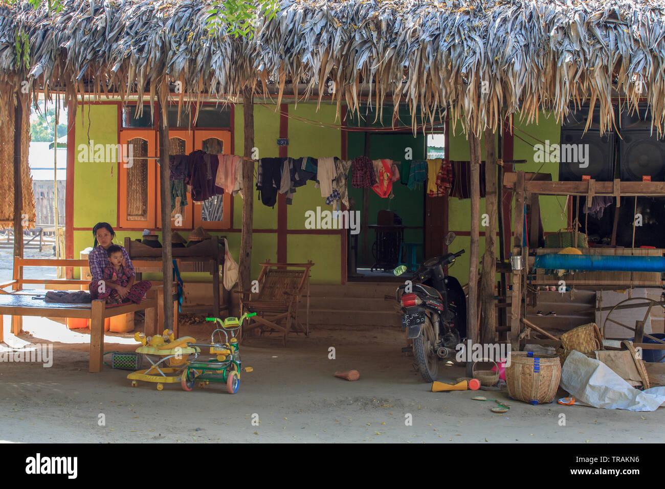 Das Leben im Dorf: junge Mutter mit ihrem Sohn sitzend vor seinem Haus Stockbild