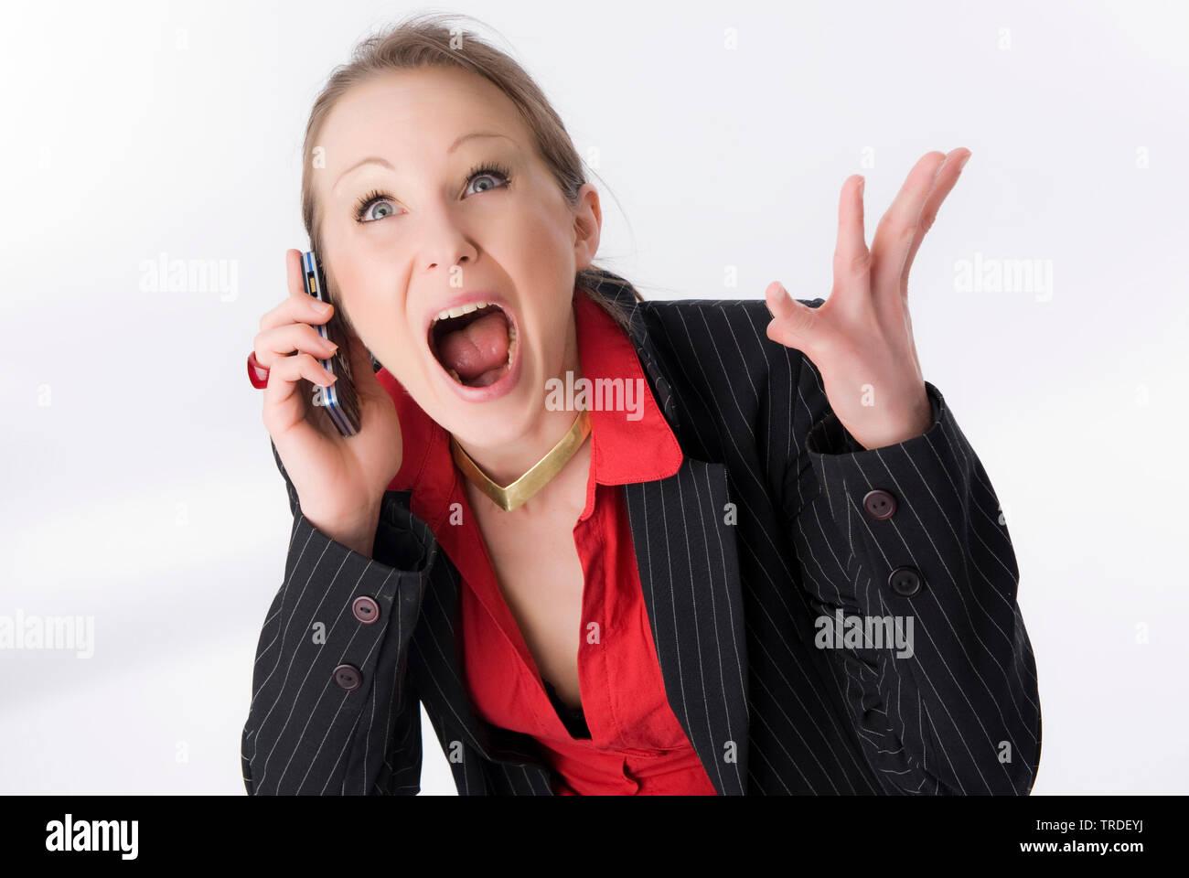 Portraet einer jungen, sympathischen Geschaeftsfrau, mit aufgerissenem Mund mit einem Handy telefonierend | Porträt einer jungen sympathischen Unternehmen woma Stockbild