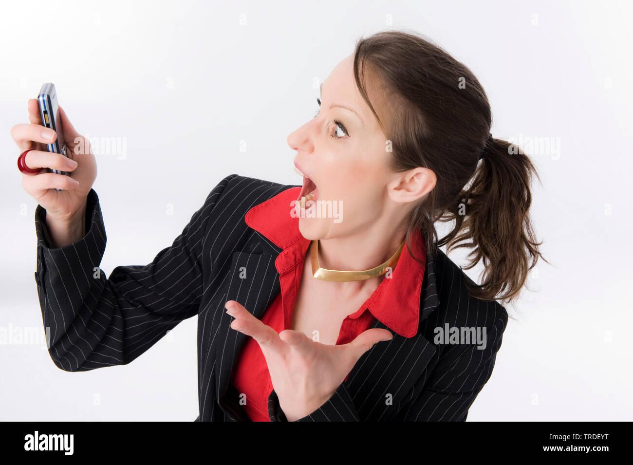 Portraet einer jungen, sympathischen Geschaeftsfrau, mit aufgerissenem Mund auf ihr Handy starrend | Porträt eines Jungen sympathische Geschäftsfrau mit Stockbild