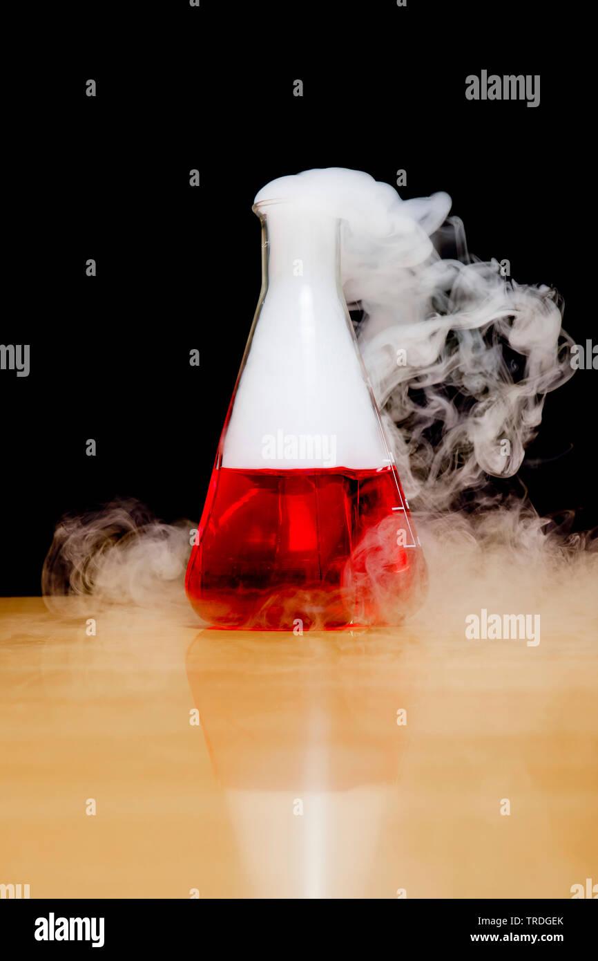 Erlenmeyerkolben mit roten Flüssigkeit und weissen Dampf auf schwarzem Hintergrund gefüllt Stockbild