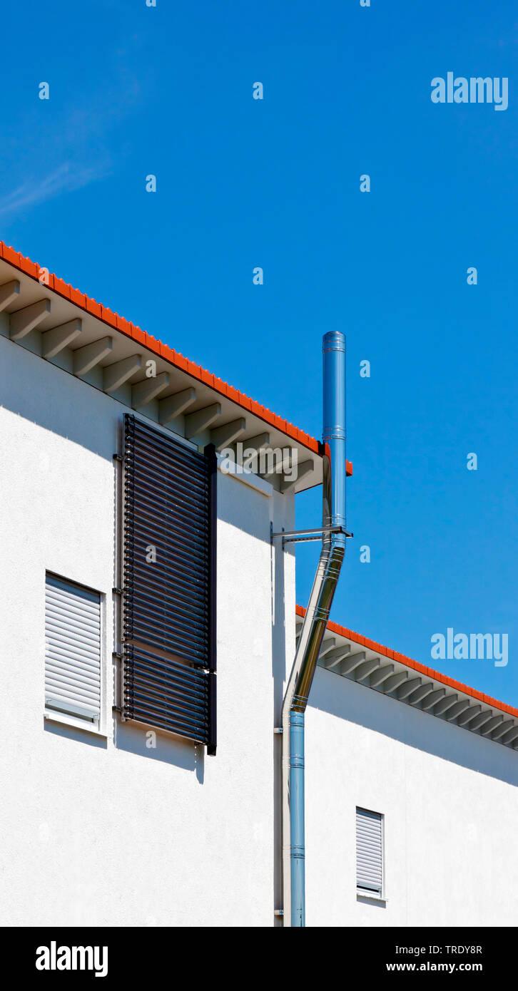 Teilansicht eines modernen Wohnhauses mit aussen liegendem Schornstein aus Edelstahl | Teilansicht eines modernen Wohnungsbau Haus mit exteriour Stapel Stockbild