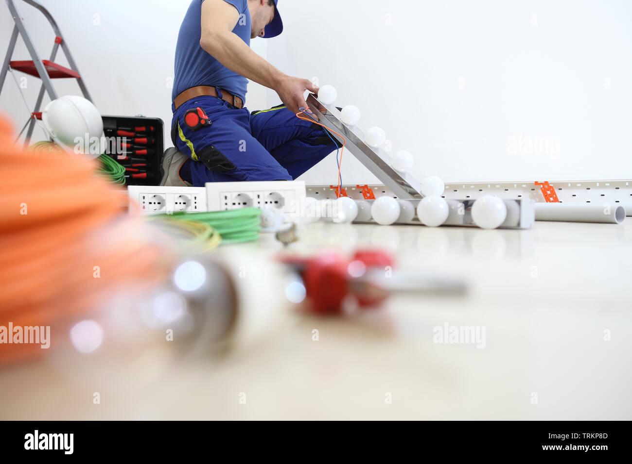 Elektriker am Werk Lampe installieren, installieren Sie Stromkreise, elektrische Verkabelung Stockbild