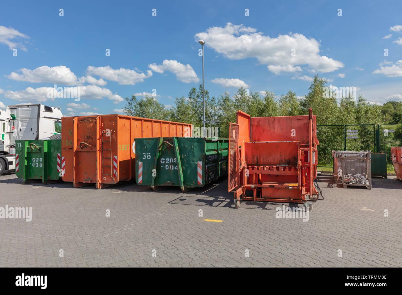 Orange abfallpressen stehen auf einem Fabrikgelände mit anderen Abfallbehälter neben Ihnen Stockfoto
