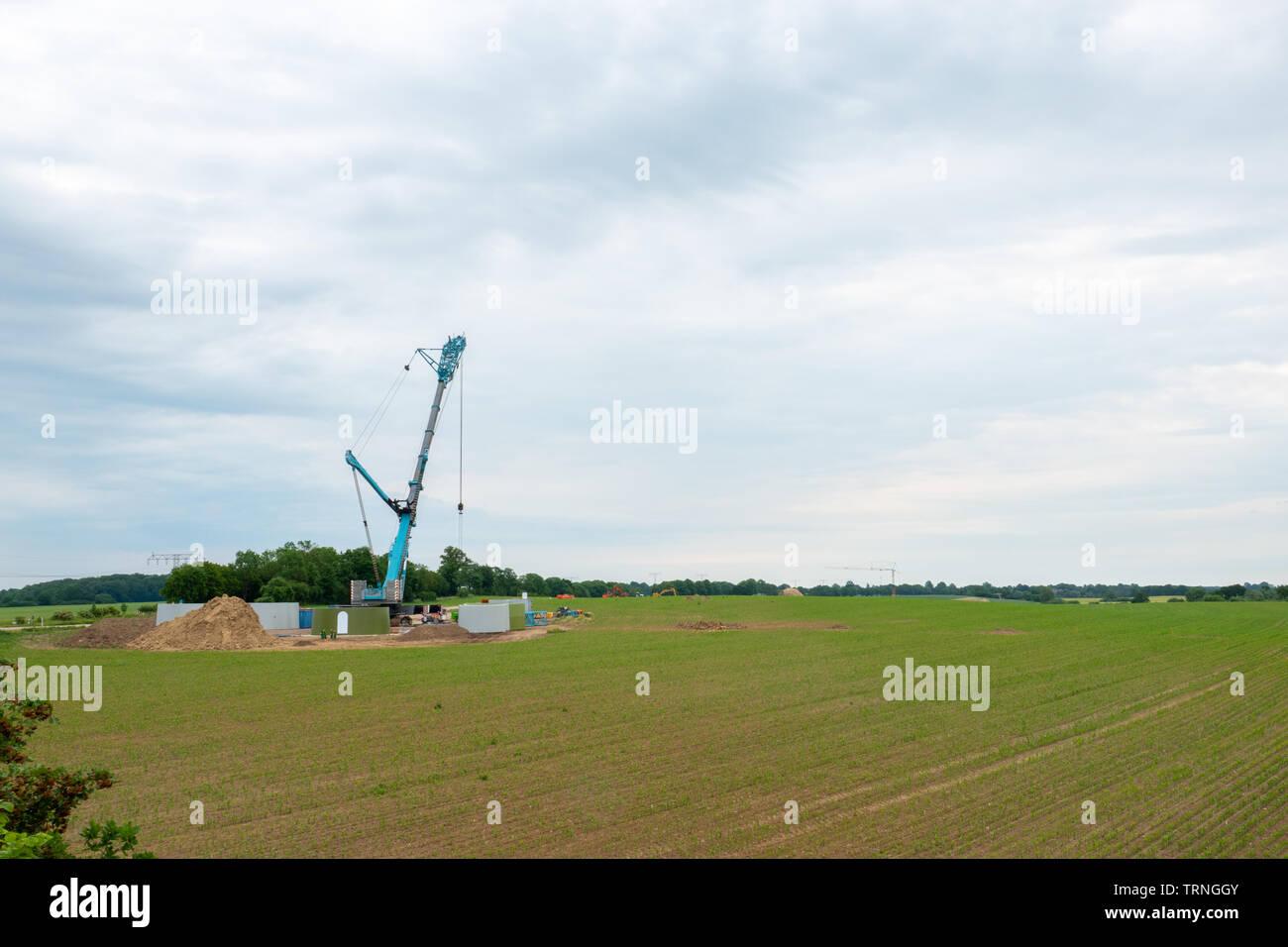 In der Mitte ein Feld, eine Windenergieanlage errichtet wird mit Hilfe von einem großen Kran Stockfoto