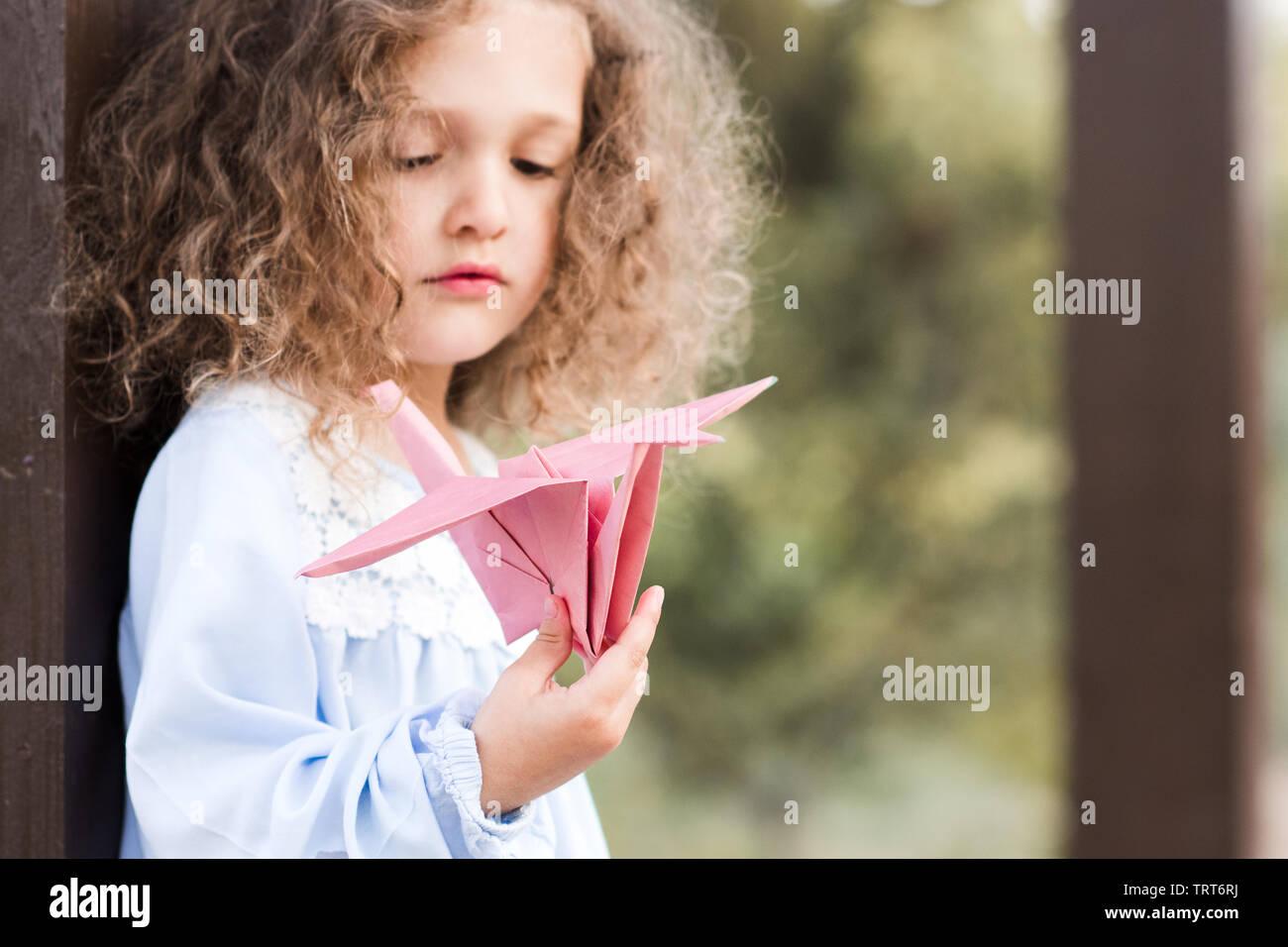 Schüler Cute Baby Mädchen 3-4 Jahre alten Holding origami Papier Kran im Freien. Stockbild