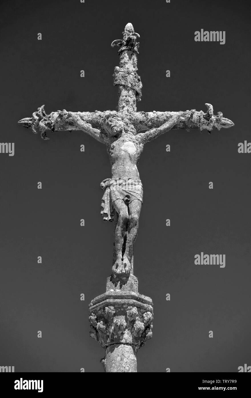 Schwarzweiß-Bild von einem Stein Statue von Christus am Kreuz auf einem Friedhof in La Feuillée, Bretagne, Frankreich. Stockfoto