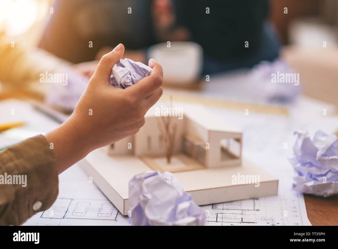 Ein Architekt vermasselt, Papiere, die von Hand, wenn das Gefühl nach Zusammenarbeit auf Architektur Modell mit shop Zeichenpapier im Amt betonte Stockbild
