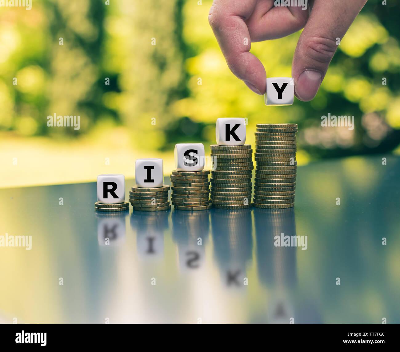 """Konzept einer zunehmenden hohen finanziellen Risiko. Würfel auf steigenden hohen Stapel von Münzen, die das Wort """"riskant"""" Form. Stockfoto"""