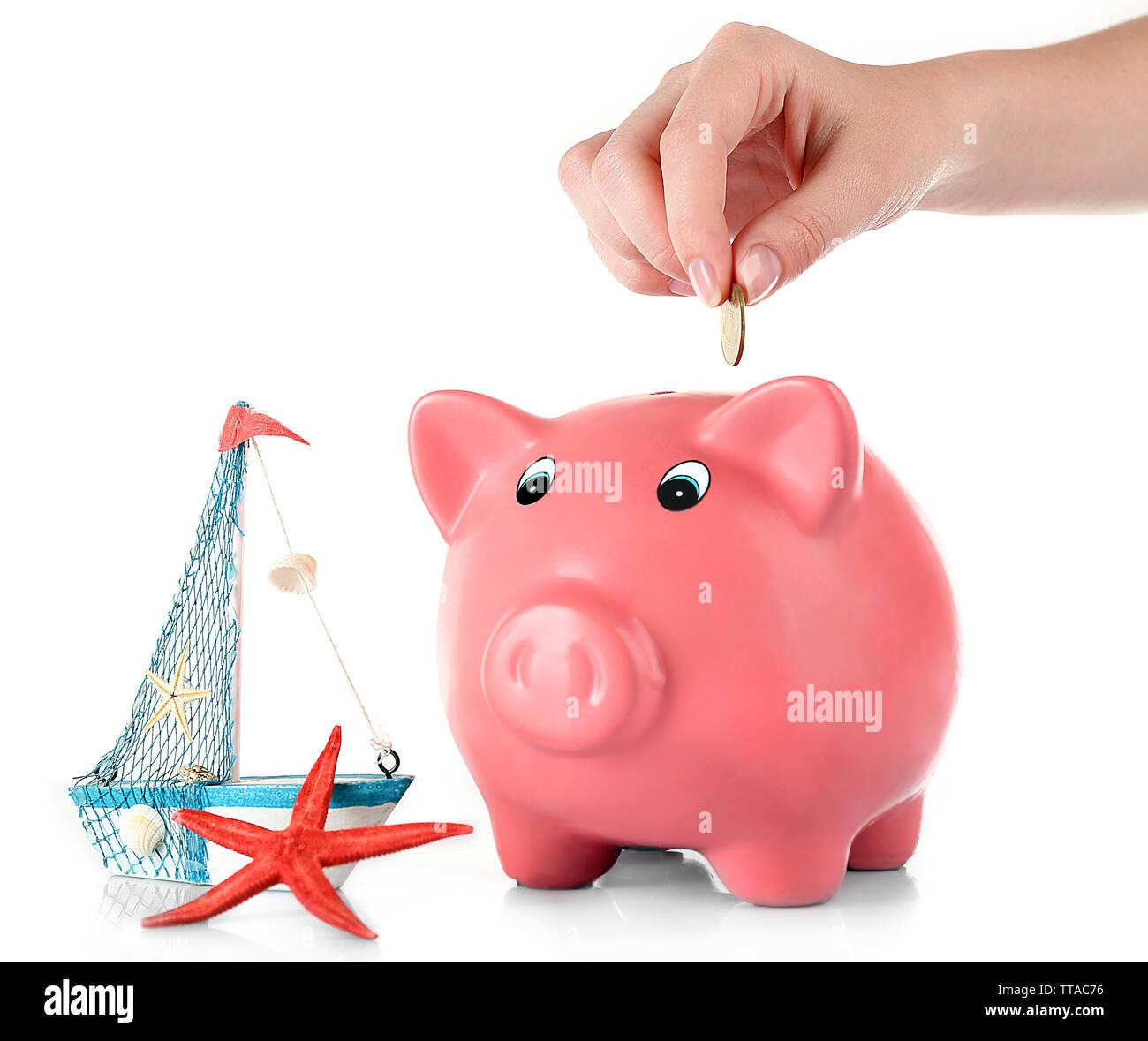 Hand stecken Geld in das Sparschwein isoliert auf weißem Stockfoto