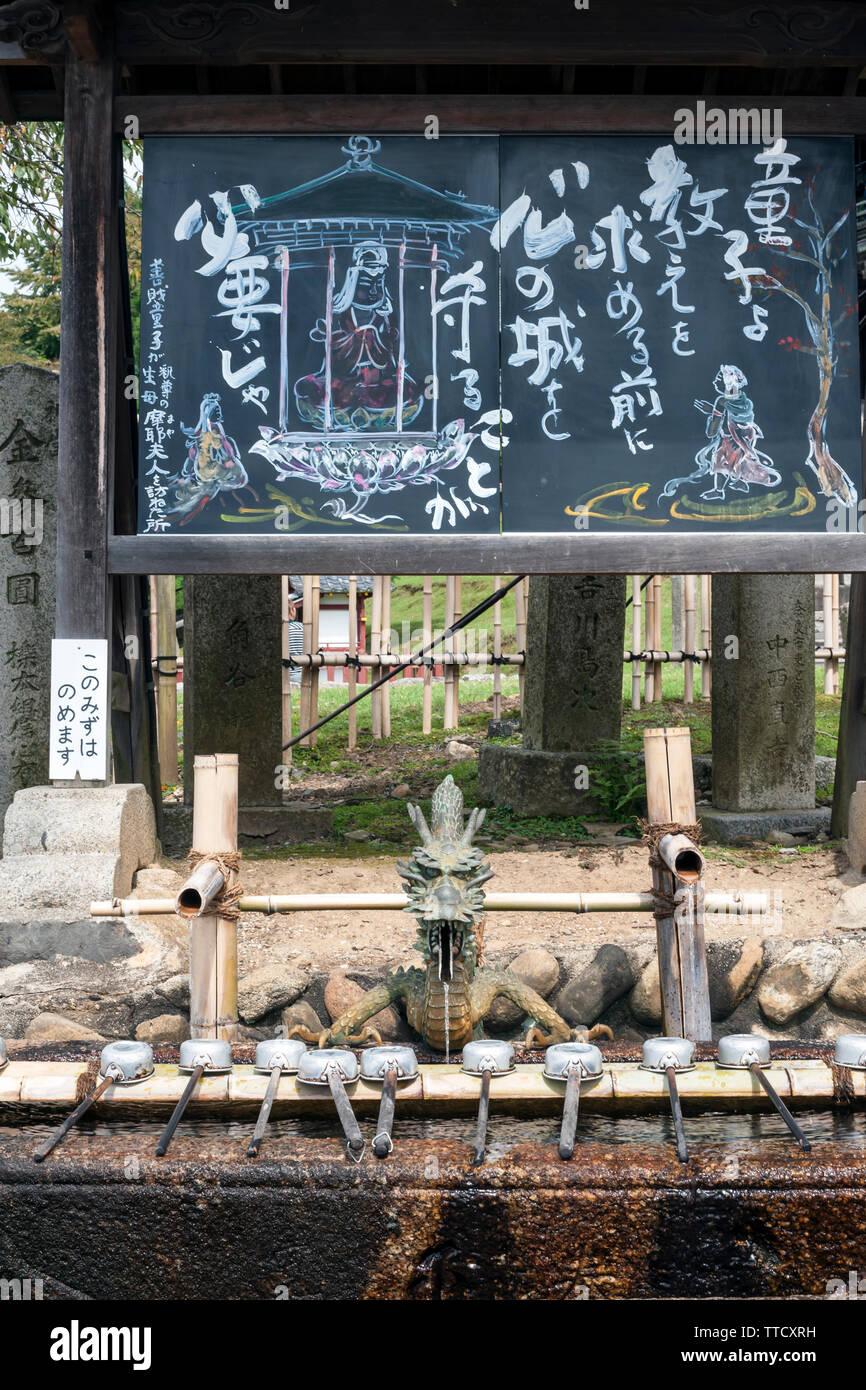 Shinto Wasseraufbereitung Becken und Pavillon (chōzuya oder temizuya) in Nara Park, Japan, betreut von einem Drachen für die Reinigung der Ritus bekannt als temizu. Stockfoto