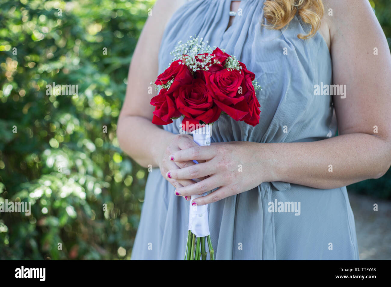 Brautjunfer holding Bouqet aus Rosen Stockfoto
