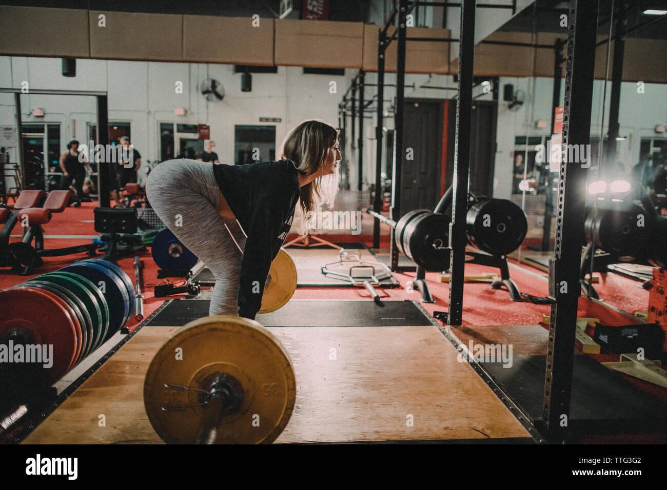 Seitenansicht des attraktiven Tausendjährigen gealterte Frau Ausbildung auf dem Squat Rack Stockfoto