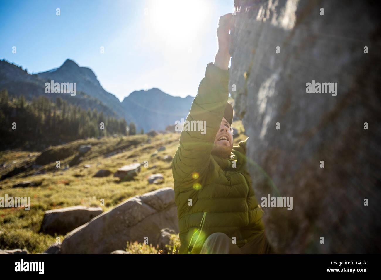 Kletterer erreicht für eine halten, während das Bouldern im Freien. Stockfoto