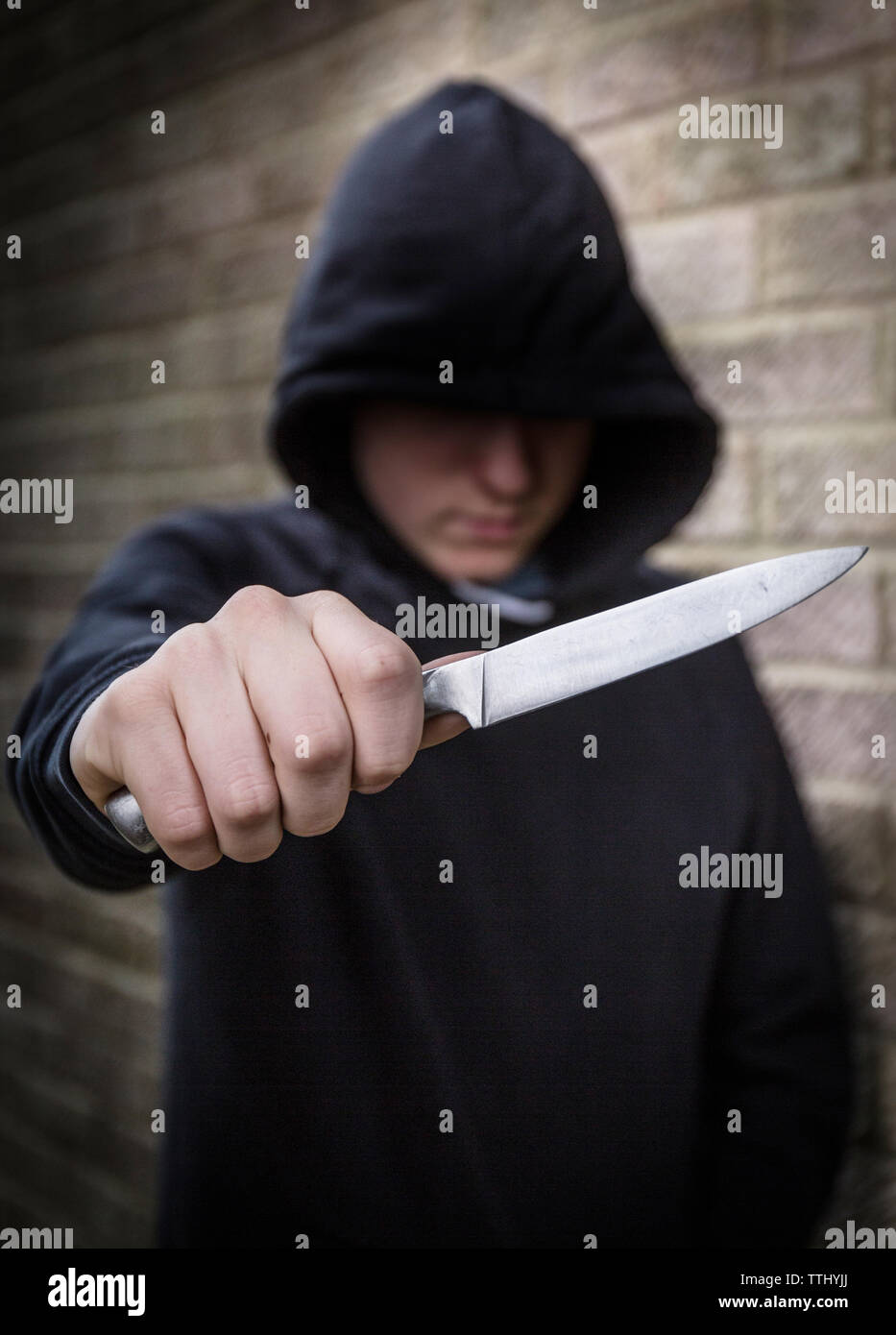 Messer Kriminalität, Teenager in der Hoody mit einem Messer auf die Straße in Großbritannien Stockbild