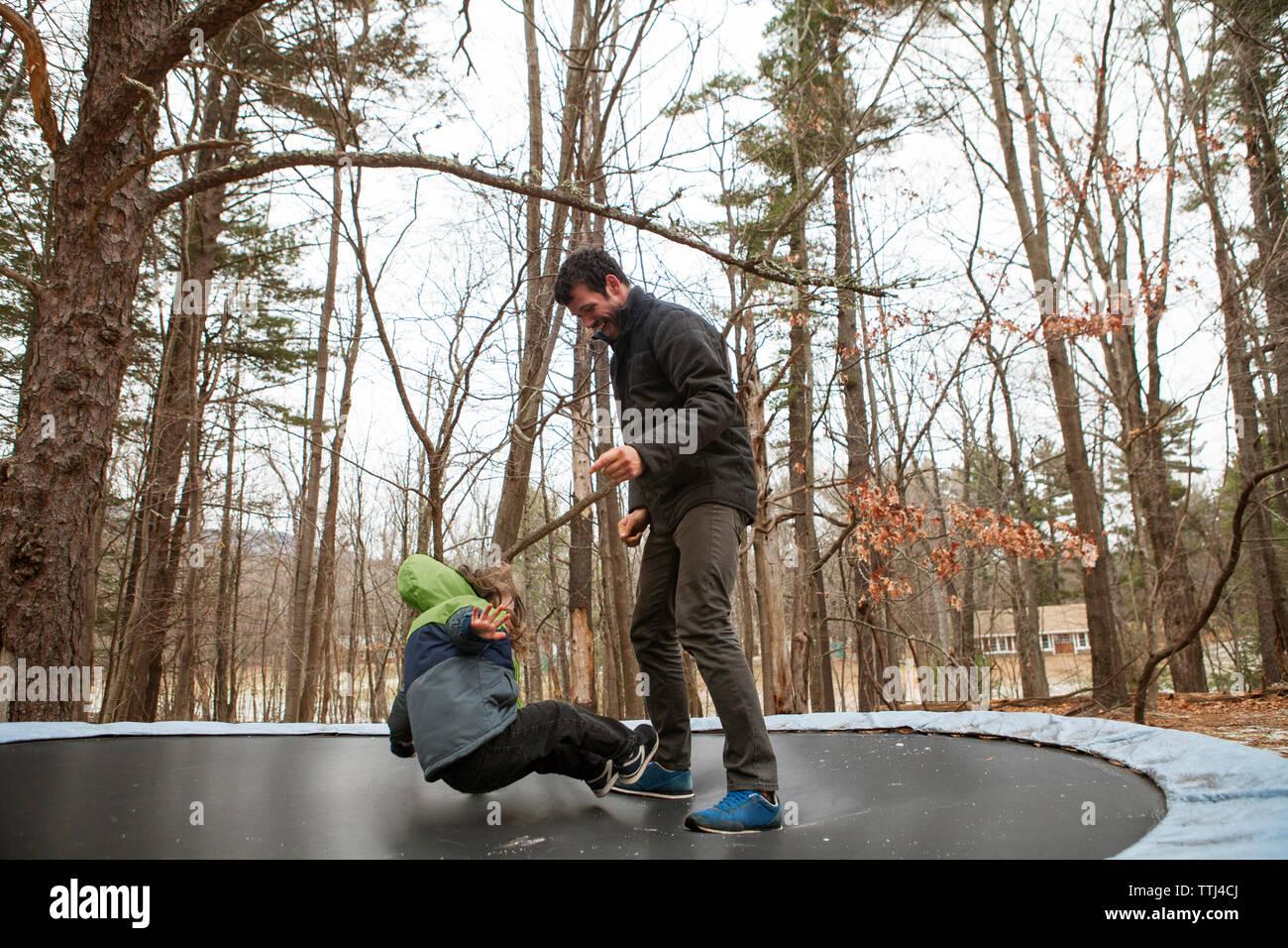 Vater auf Sohn springt auf einem Trampolin im Park Stockfoto
