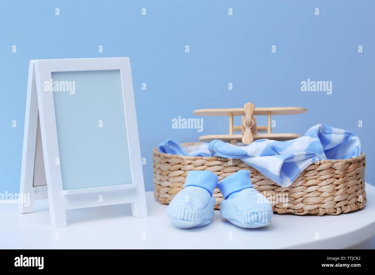 Baby Kleidung und Rahmen auf der blauen Wand Hintergrund Stockbild