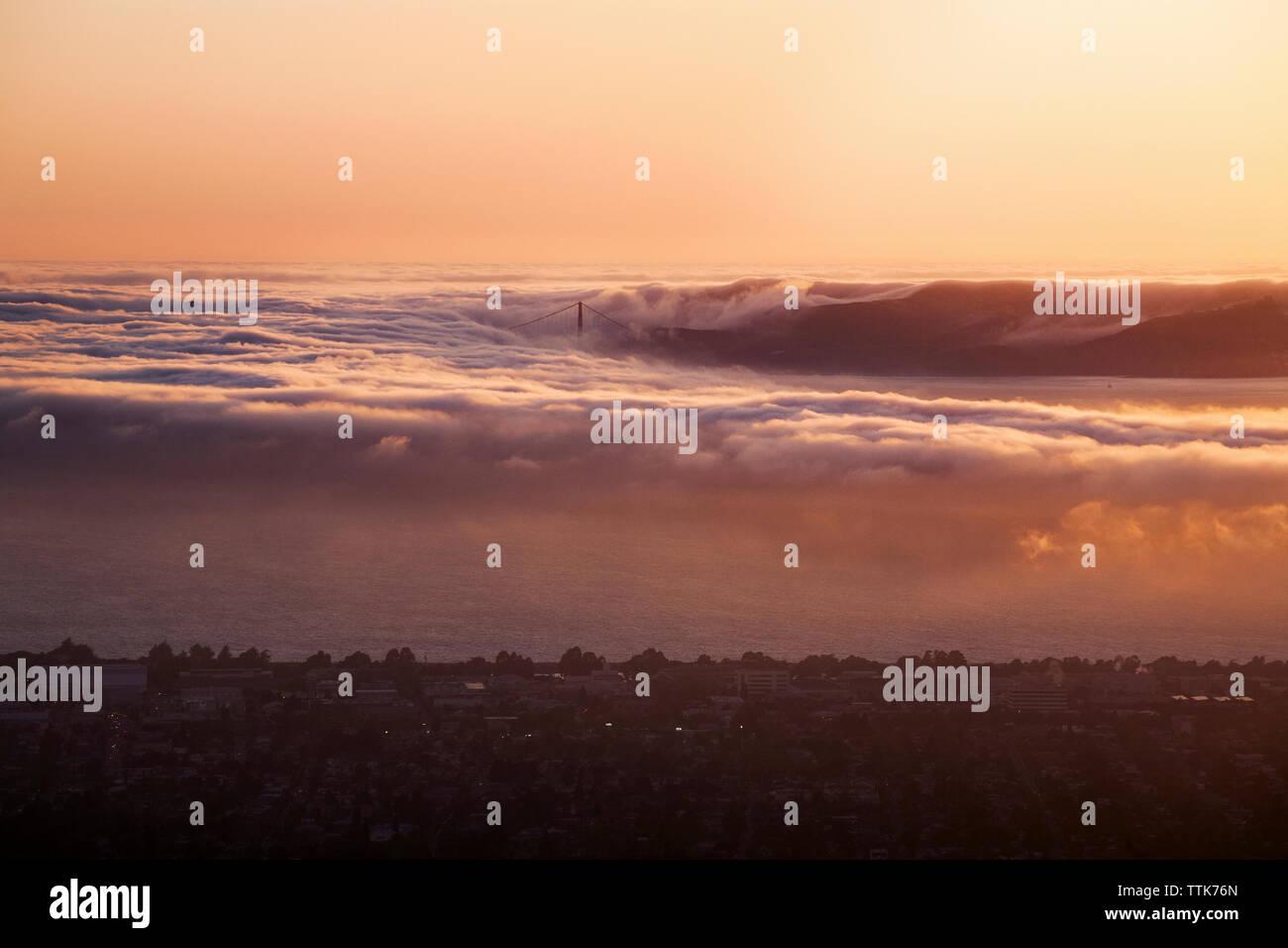 Digitale zusammengesetzte Bild von Wellen und die Stadt bei Sonnenuntergang Stockbild