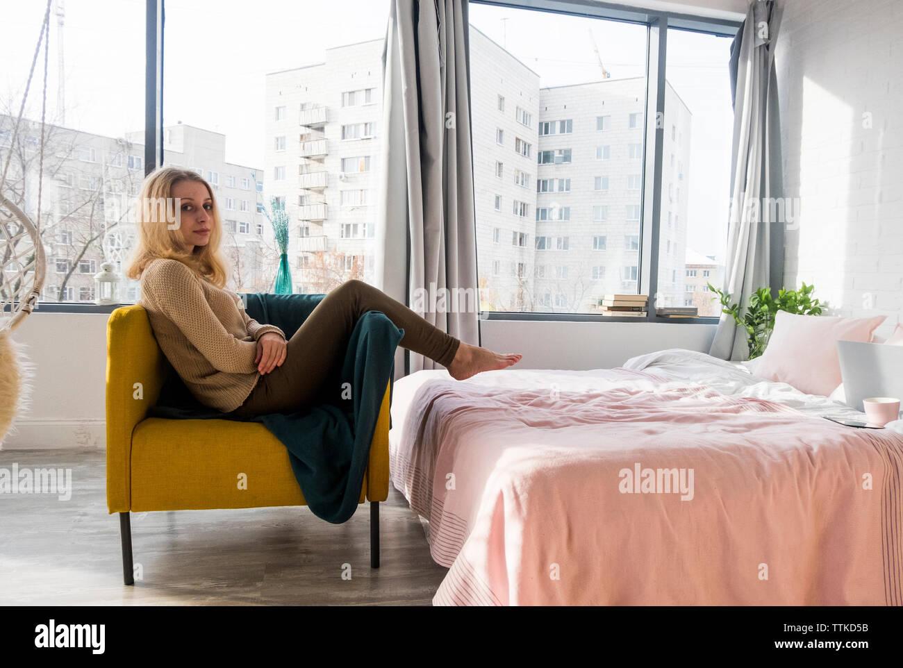 Portrait von Frau entspannend auf Sessel im Schlafzimmer zu ...