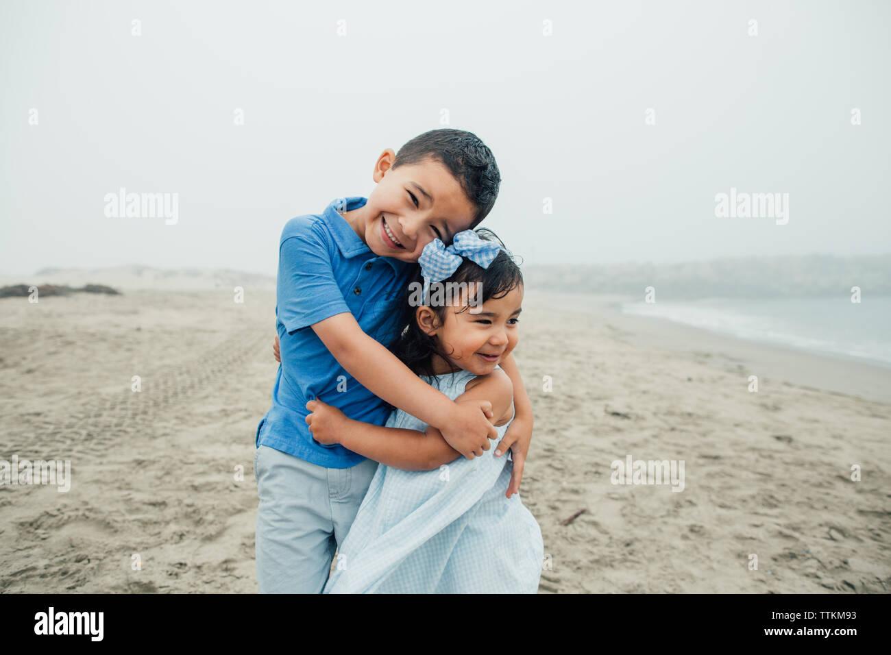 Junge Bruder und Schwester umarmen, während Sie die Wellen an nebligen Strand Stockfoto