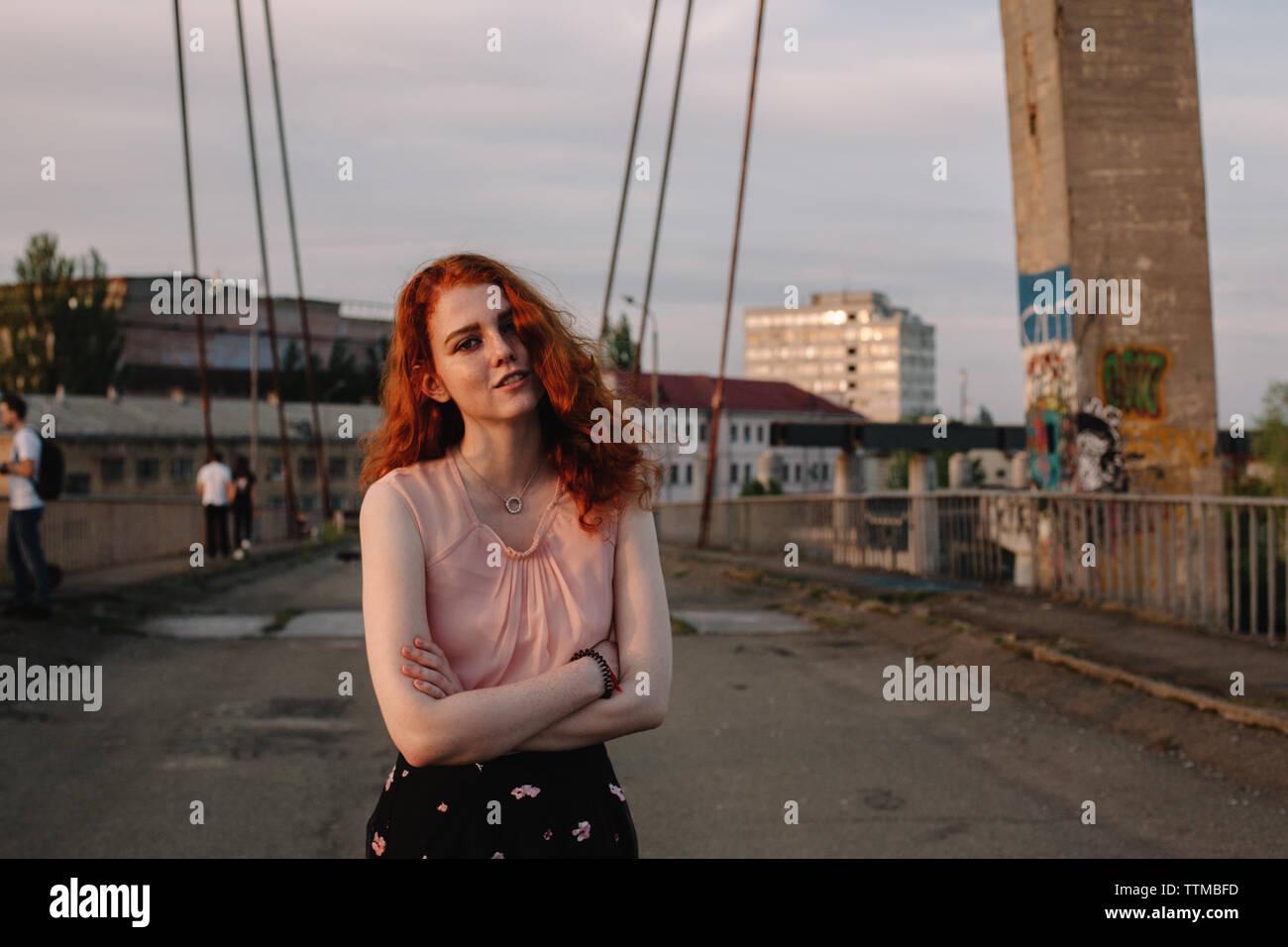 Porträt der jungen Frau mit roten Haaren steht auf der Brücke in der Stadt Stockfoto