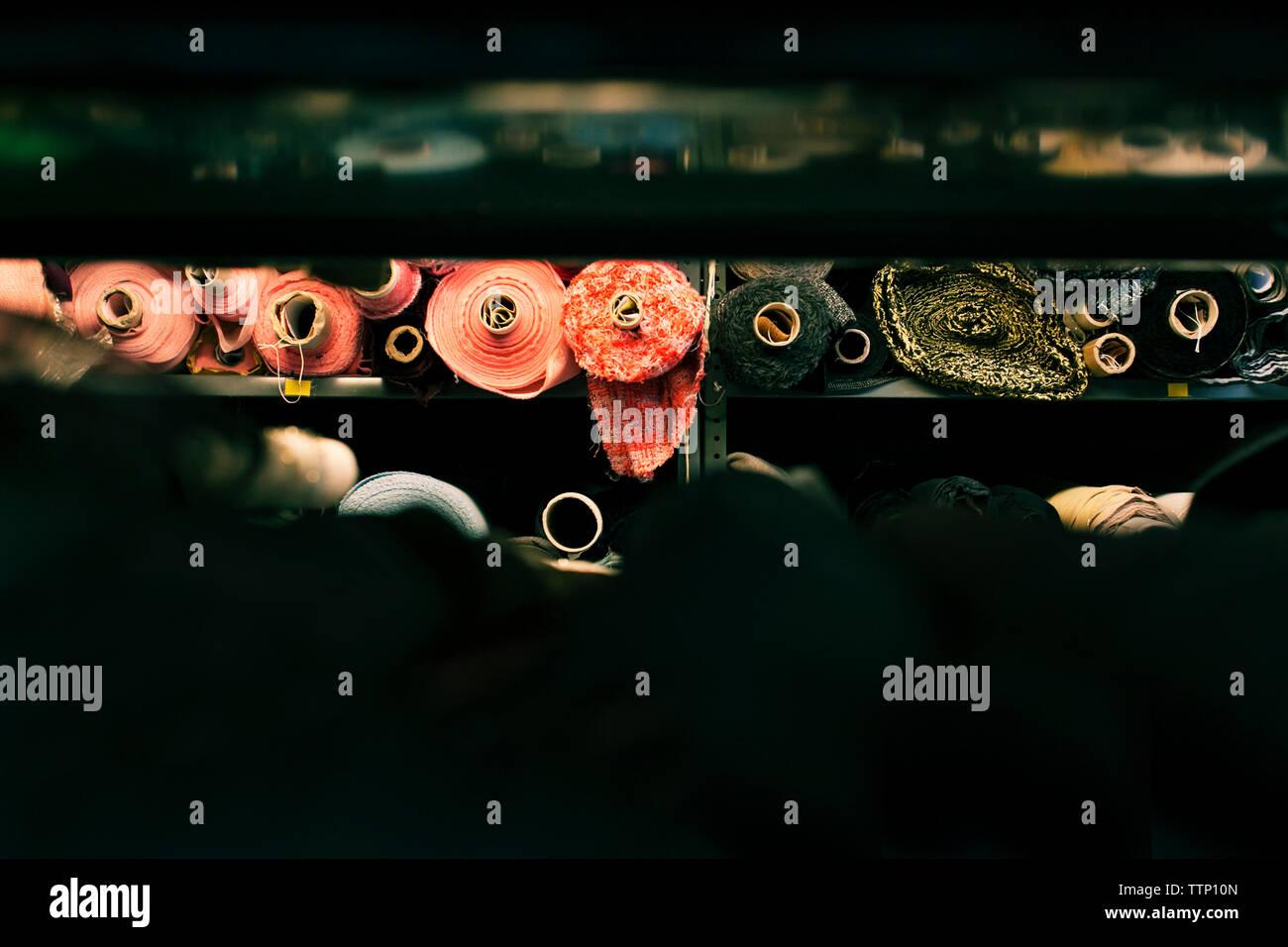Verschiedene Stoffe in Regal gerollt Stockfoto