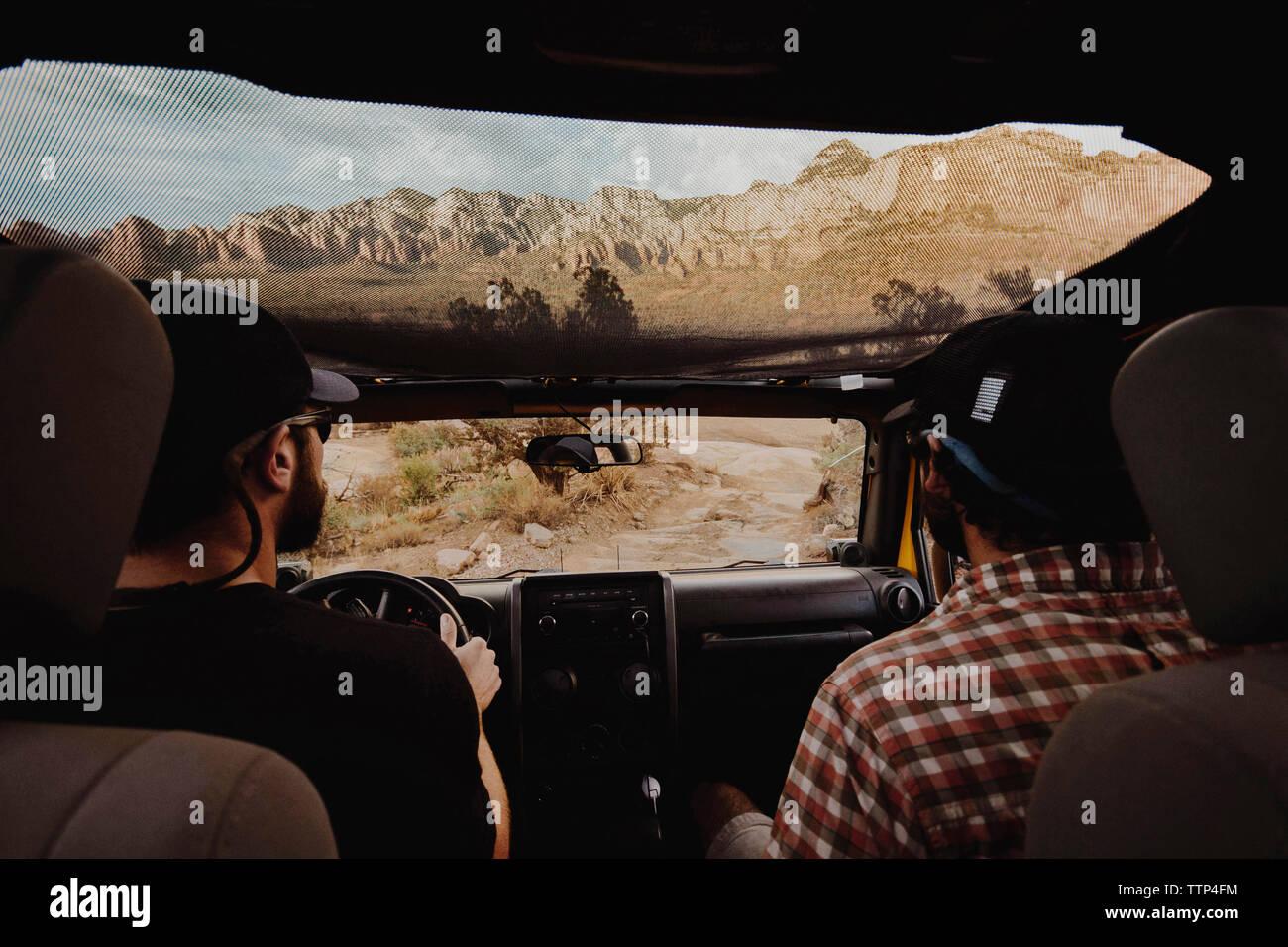 Ansicht der Rückseite des Freunden unterwegs in Geländewagen auf unbefestigte Straße Stockbild