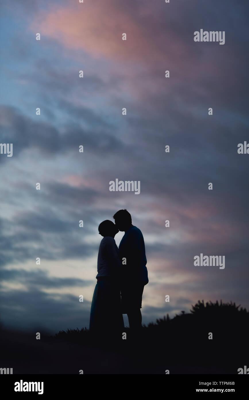 Silhouette paar Küssen beim Stehen auf Feld gegen bewölkter Himmel bei Sonnenuntergang Stockfoto