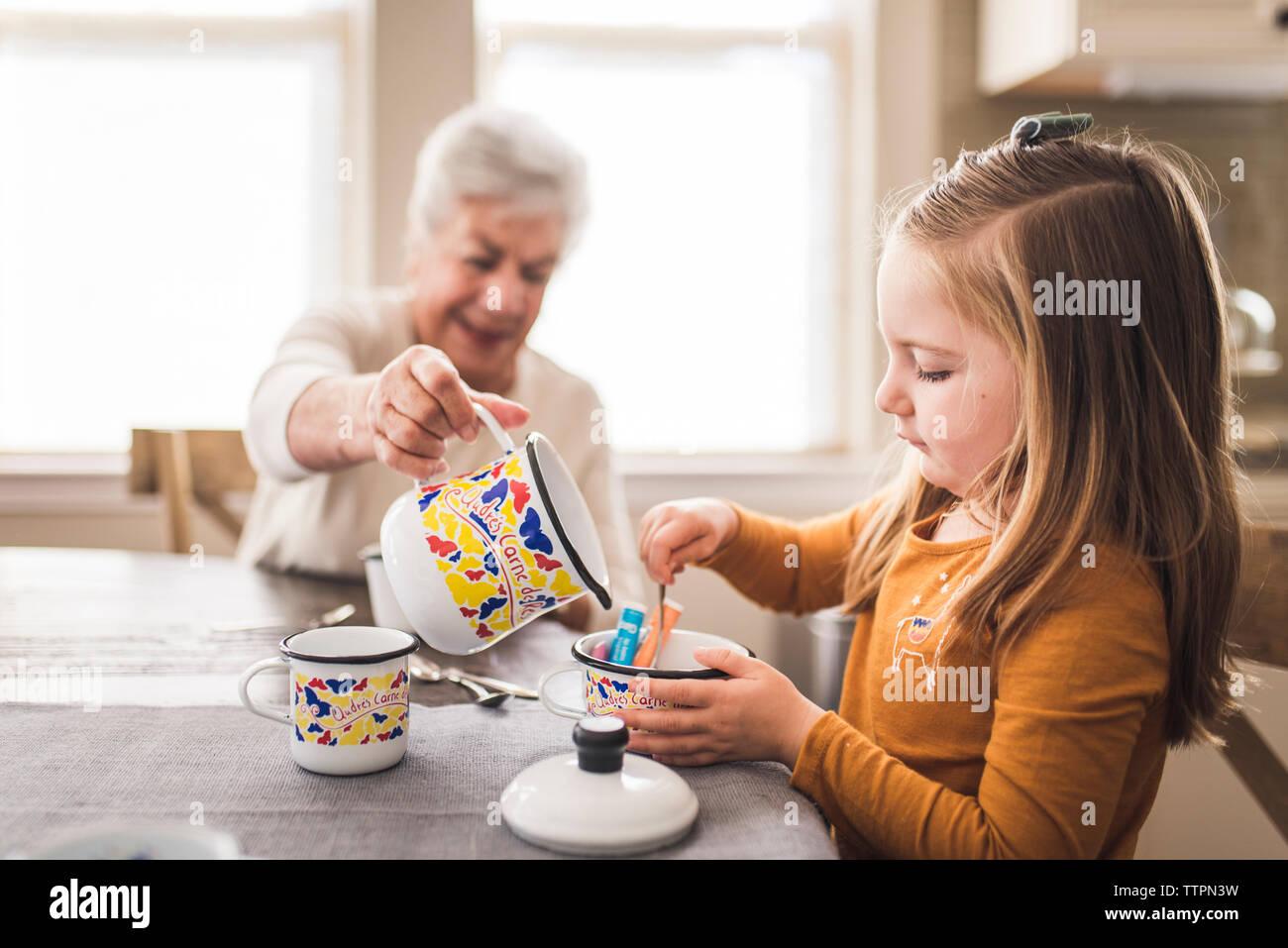 Enkelin und große Großmutter in der Küche spielen mit Tee Set Stockfoto