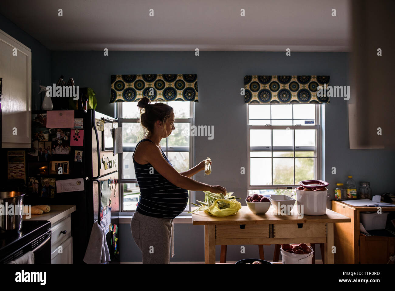Die werdende Mutter schalen Mais in hell erleuchteten Küche Stockfoto
