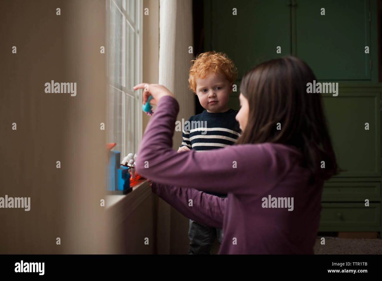 Kleinen Bruder aufpassen grosse Schwester spielen mit Spielzeug zu Hause Stockfoto