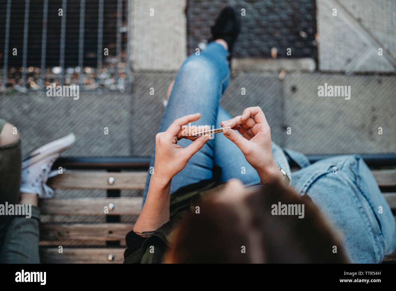 Junge Frau rolling Zigarette auf der Bank sitzen Stockfoto