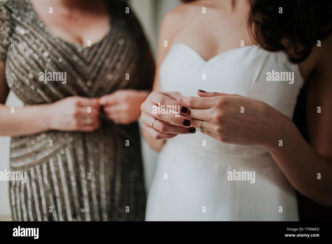 Mittelteil der Braut mit einem Hochzeitskleid Kleid im Stehen durch die Brautjungfer Stockbild