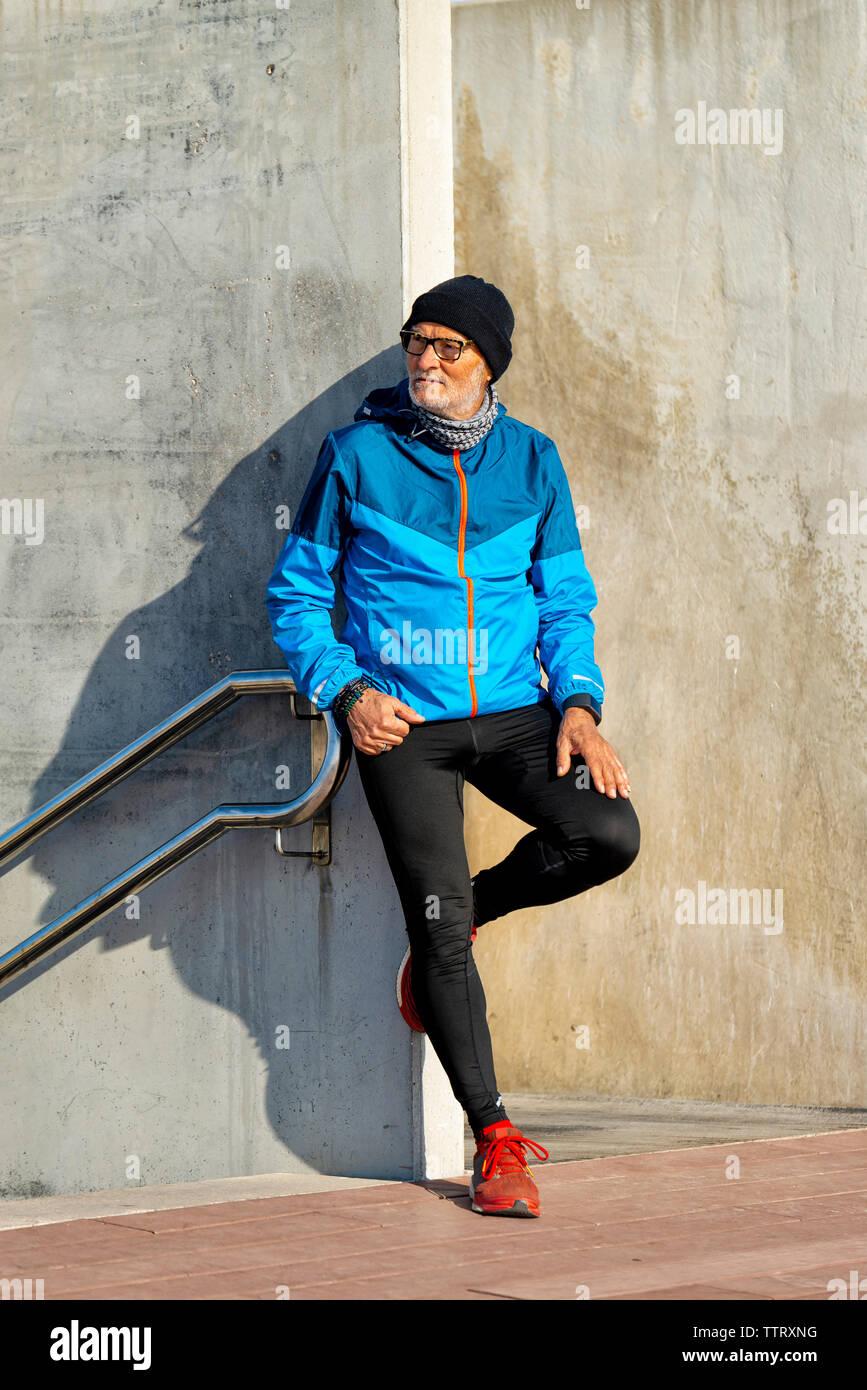 Ältere Menschen tragen sportliche Kleidung lehnte sich auf Wand, während Sie auf der Suche Stockfoto
