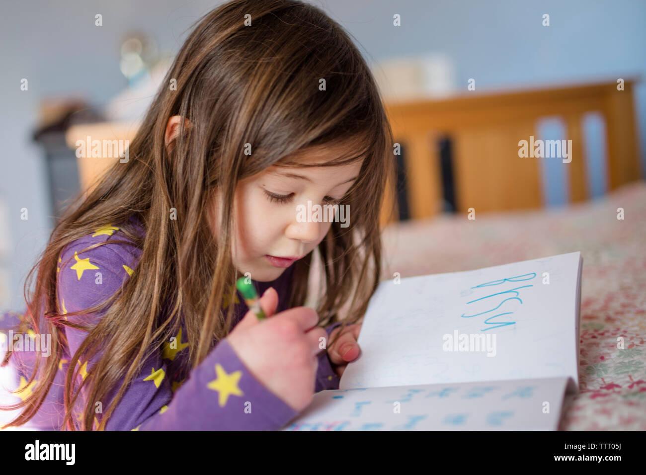 Ein kleines Mädchen leise arbeitet in ihrem Bett Wörter in ein Buch schreiben Stockfoto