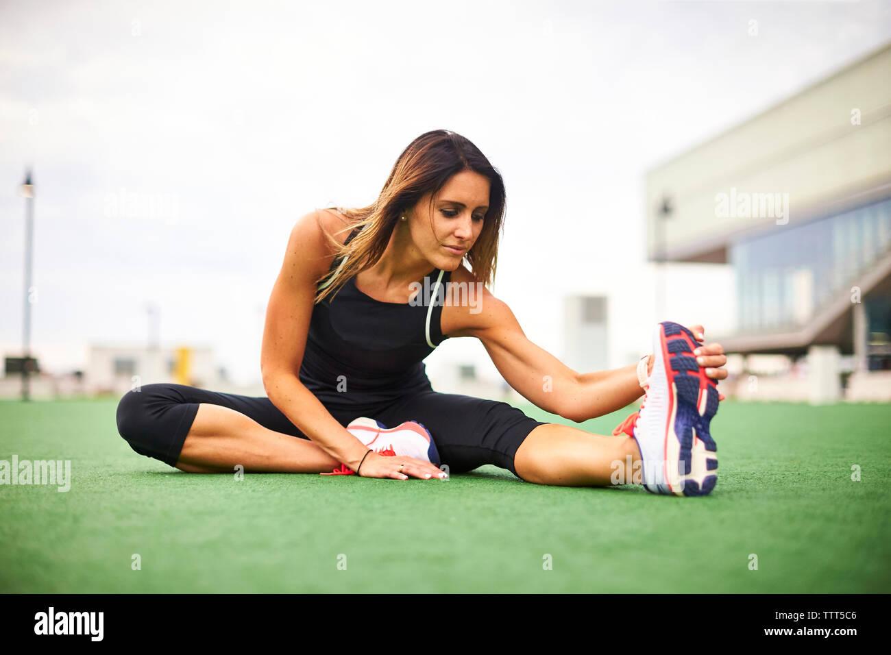 Eine sportliche Frau, die sich auf Rasen. Stockfoto