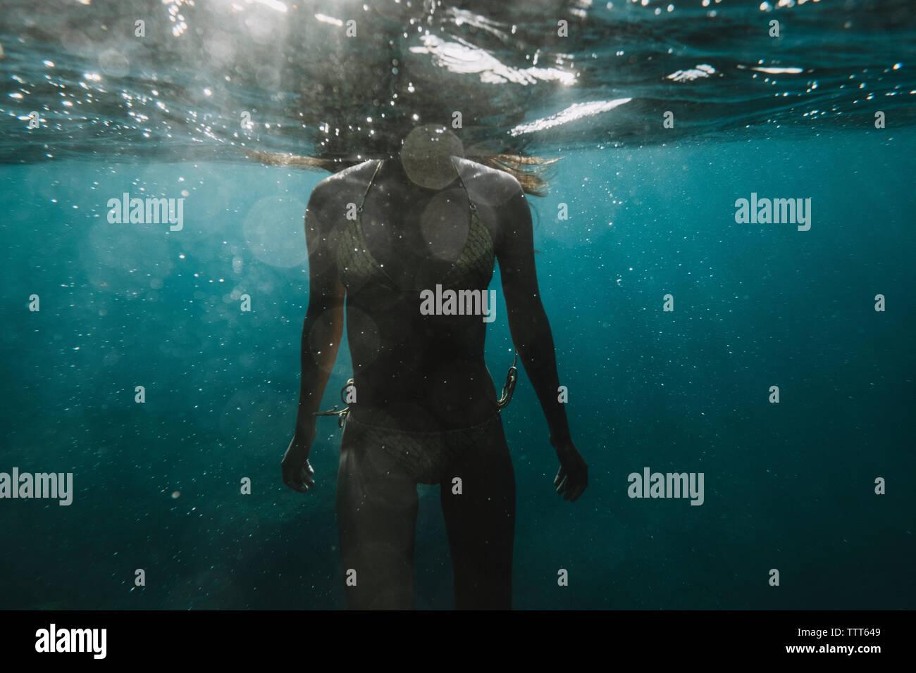 Dramatische teilweise unter Wasser Blick auf eine Frau im Bikini Stockfoto