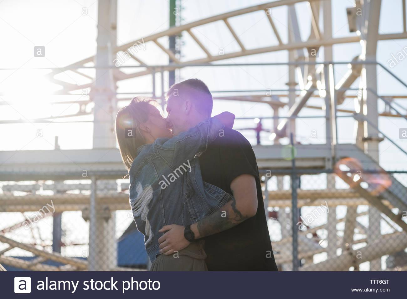 Leidenschaftliche paar Küssen, während sich gegen Vergnügungspark Stockbild