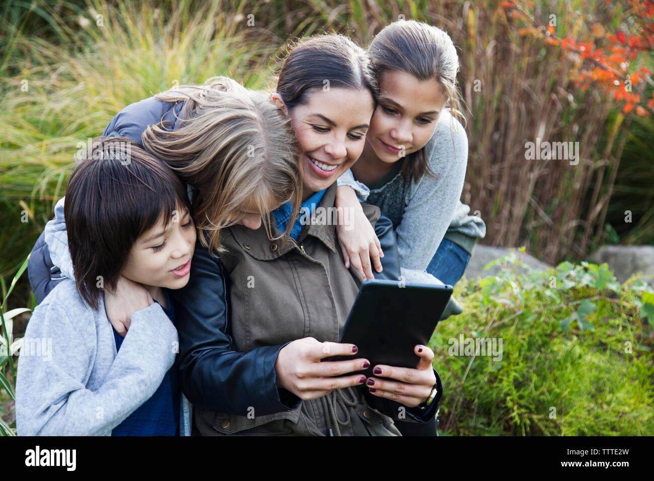 Lehrer zeigen Tablet Computer für Kinder während der Exkursion Stockfoto