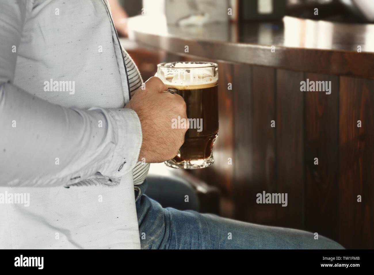 Mann hält ein Glas Bier in der Kneipe, Nahaufnahme Stockbild